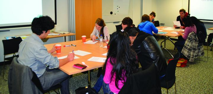 Two groups of students sitting at two tables working with papers on the tables