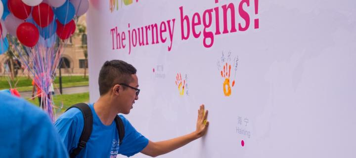A student puts his handprint on a welcome wall at Zhejiang