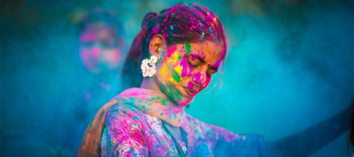 Woman covered in colours during Indian Holi festival