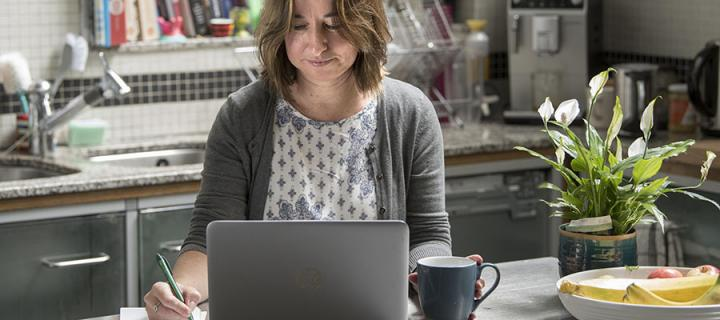 Woman studying on laptop in kitchen