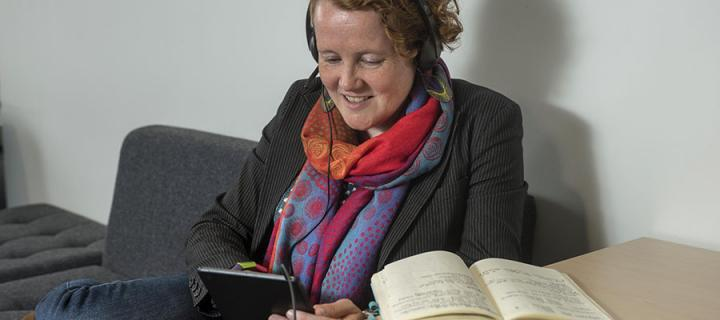 Woman using tablet with notebook and headphones