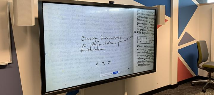 a large screen shows a close-up image of a manuscript