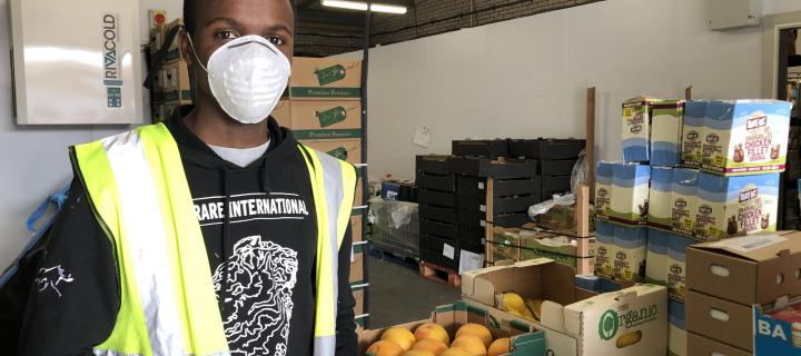 A volunteer stands in front of food he is organising for distribution
