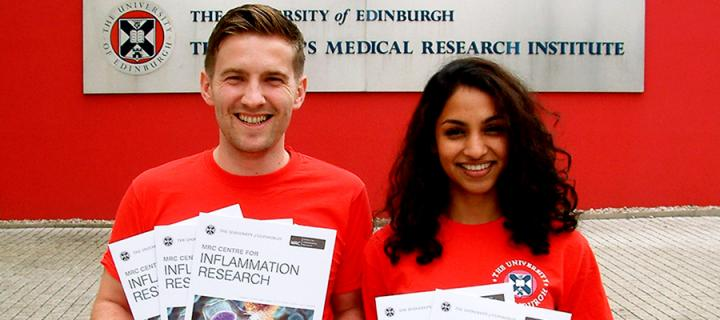 Two young medical researchers holding leaflets about the MRC Centre for Inflammation Research