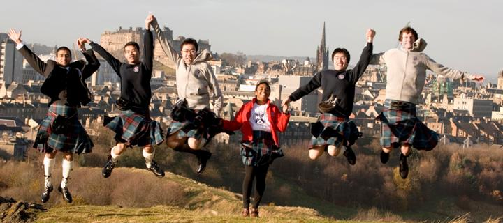 Group of students jumping outside, with a backdrop of the University campus.