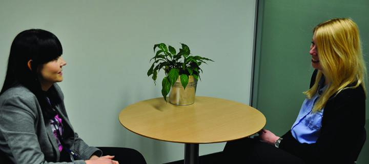 A member of Careers Service staff and a student sitting at a table having a discussion