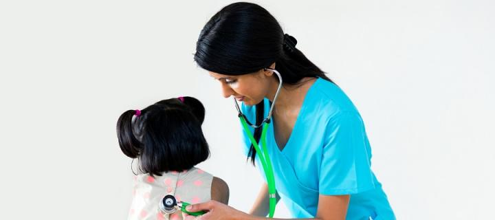 Child with health professsional and stethoscope