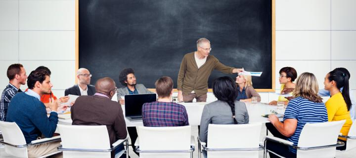 Individuals gathered around a round seminar table in front of a blackboard