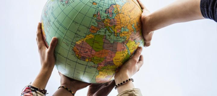 Hands of different individuals holding an Earth globe high