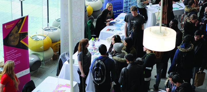 Several information stands with students and employers at a careers fair in the Informatics Forum