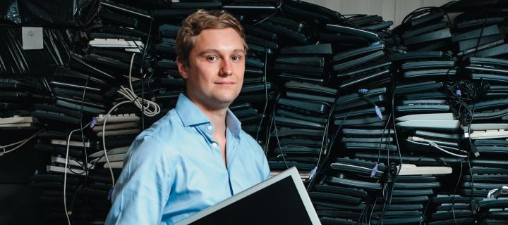 James Turing standing in front of a high stack of used PC hardware