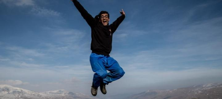 Man jumping in air on top of a mountain