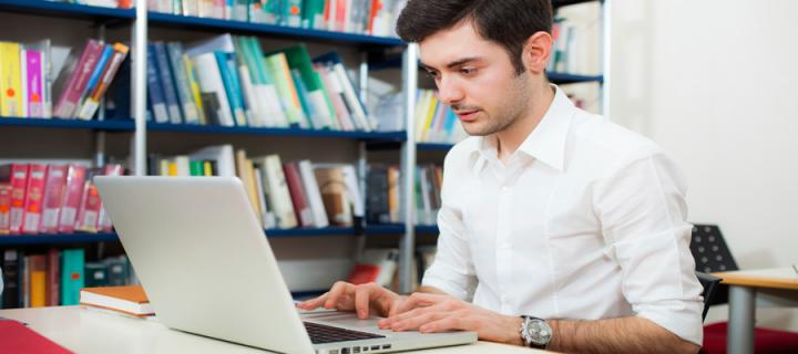 male student at laptop in library image