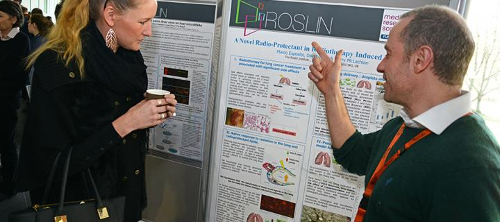 Student at a poster board explaining research