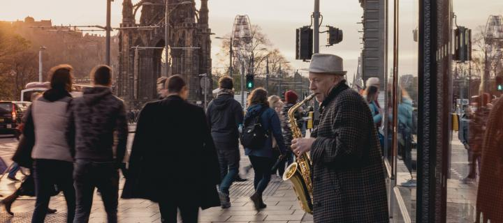 Princes Street in Edinburgh with a man playing saxophone