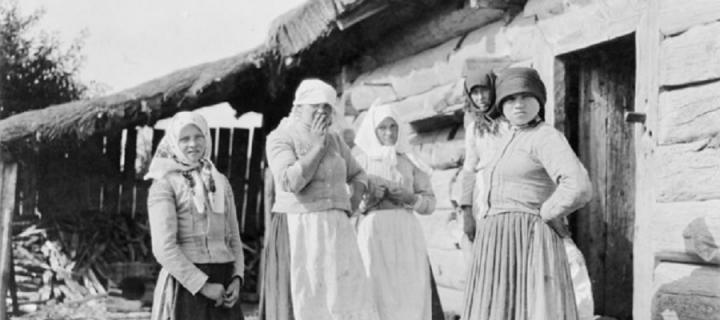 Five peasant women standing outside of log house
