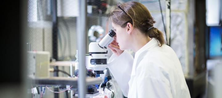 A Neurologist looks through a microscope