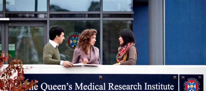 Photograph showing people chatting outside the Queen's Medical Research Institute