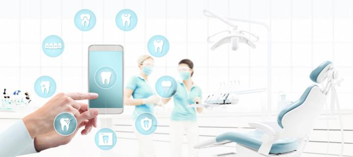 mobile phone surrounded with icons held by hand with dentist chair