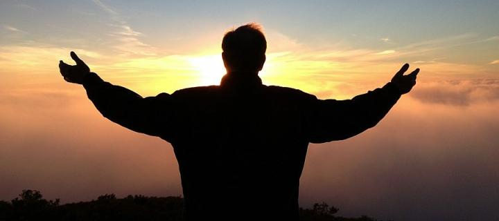 Man in silhouette against sunset with arms raised as if in thanks or prayer