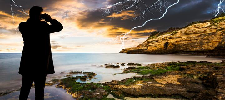 Man with binoculars looking out at a lightning storm from some rock pools