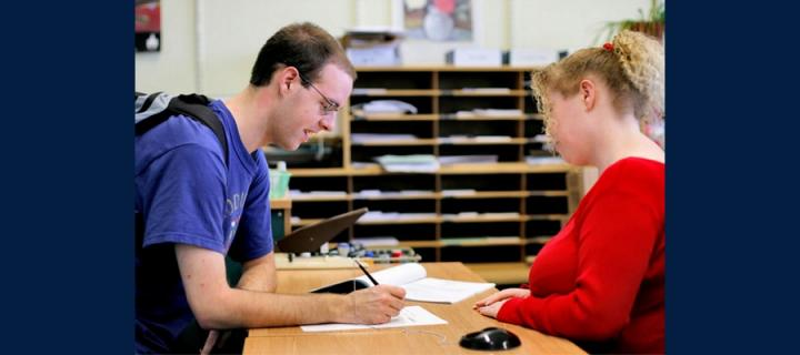 Student submitting paper to staff member