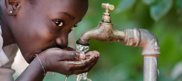 Photo of an African child drinking water from a tap