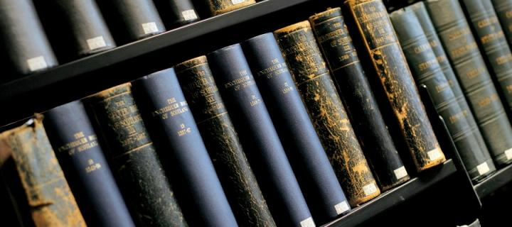 A library shelf full of old blue, brown and grey books.