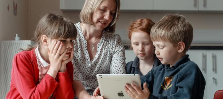 Researcher looking at an ipad with 3 children