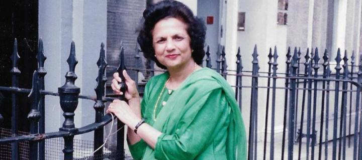 Saroj Lal wearing a green sari standing by railings on Forth Street