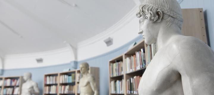 Classical statues in front of book cases