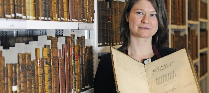 researcher with book from Adam Smith's library