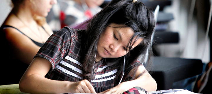 Female student studying with headphones on