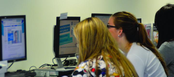 Two female students working at computers in the Careers Service office in the Main Library Building