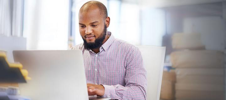 Photo of a male working on a laptop