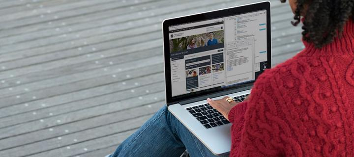 Photo of a female student browsing the University website on a laptop