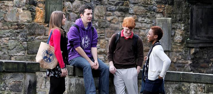 Photo of students chatting in Greyfriars Kirkyard in Edinburgh's Old Town with the Castle in the background.