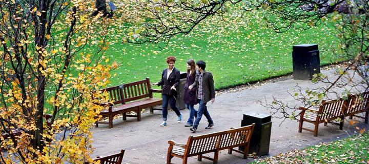 Photo of students walking through Princes Street Gardens below Edinburgh Castle.