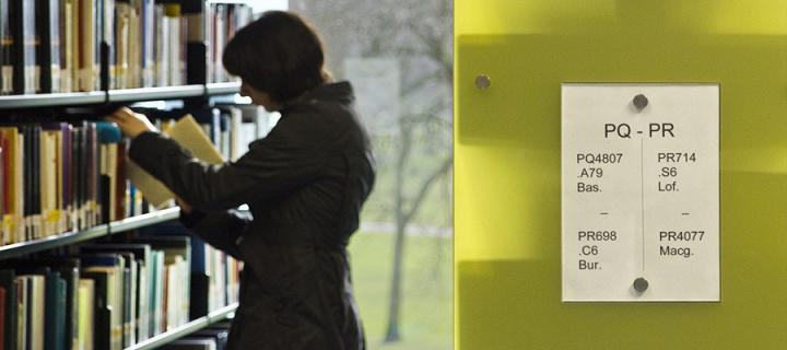Woman putting book on library shelf