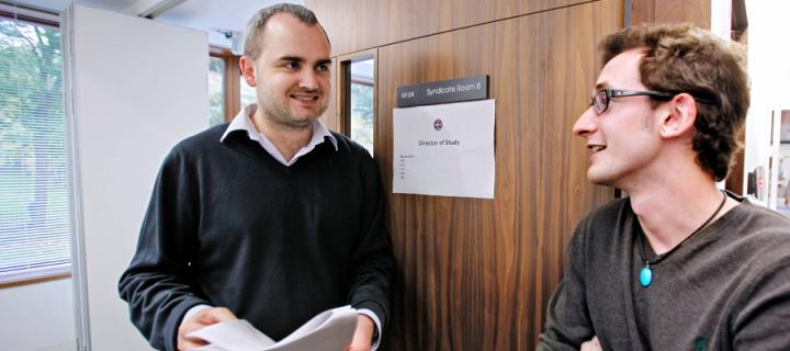 A male lecturer talking with a male student in the Business School