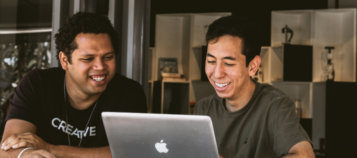 Two men smiling and looking at a laptop