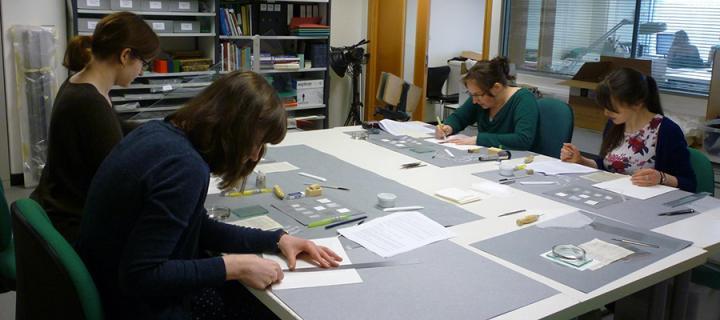 Volunteers   receiving training in the conservation studio