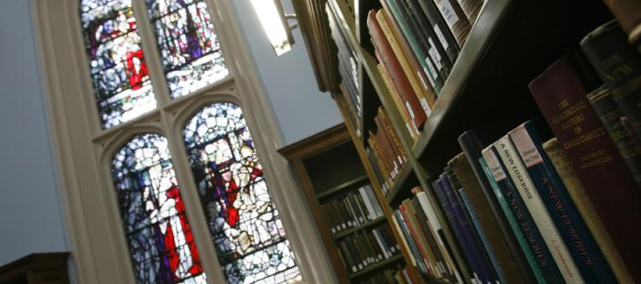 Books in front of stained glass window
