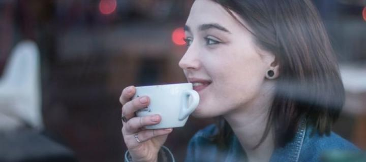 Woman looking out cafe window with coffee in hand