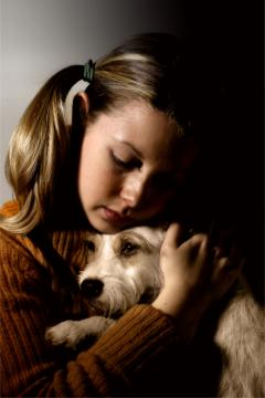 Photograph of a girl hugging a dog