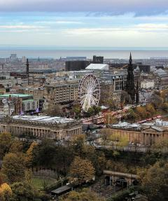 A view across Princes Street Gardens with a ferris wheel and the Scott Monument prominent