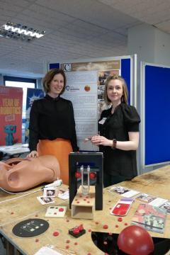 Dr Helen Szoor-McElhinney and Dr Melanie Jimenez (University of Glasgow) stand with some public engagement items