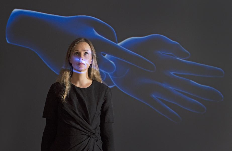 Caroline Grewar, manager of the University of Edinburgh's Talbot Rice Gallery, stands before artist Marjolijn Dijkman's projection of two virtual hands.